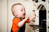 Unguarded baby with open oven — Stock Photo