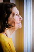 Solitude - senior woman looking through window — Stock Photo