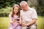 Grandchild shows grandfather smartphone — Stock Photo