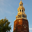 Ancient tower with clock in the historical city center of Amsterdam - Stock Photo