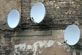 Satellite dish antenna on the old house wall  — Stock Photo