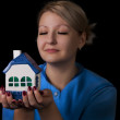 Woman holding a small house — Stock Photo