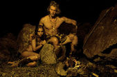 Primitive man and his woman sitting near the fire in the cave — Stock Photo