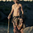Primitive man standing near his woman. — Stock Photo