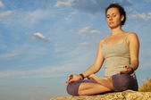 Young woman practicing yoga on the stone at the sky background — Stock Photo