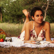 Brunette beautiful woman reading book on a meadow — Stock Photo #50897559