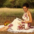 Brunette beautiful woman reading book on a meadow — Stock Photo #50897561