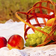 Постер, плакат: Picnic basket with fruits on grass in summer park
