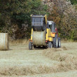 Machine with straw bales, the ball goes out of the press — Stock Photo