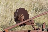 Old agrarian equipment, abandoned in a field — Stock Photo