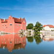 Red castle in the middle of pond — Stock Photo