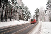 Red van on winter road — Stock Photo