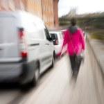Blurred woman on sidewalk — Stock Photo