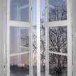 Winter sunset viewed through old window — Stock Photo