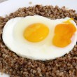 Roasted eggs on portion of buckwheat gruels as vegetarian meal — Stock Photo #12440243