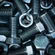 Closeup of black nuts and bolts background — Stock Photo