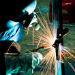 Human working of welding with a lot of sparks in a metal industr — Stock Photo