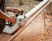 Carpenter working with electric planer in his workshop — Stock Photo