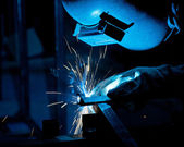 Human working of welding with a lot of sparks in a metal industr — Stockfoto