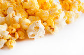 Salted popcorn grains on the white background — Stock Photo