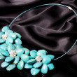 A bead necklace with flowers on black background — Stock Photo #19843613