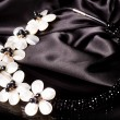 A bead necklace with flowers on black background - Stock Photo