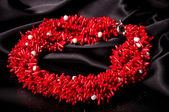 Beautiful red necklace on black material — Stock Photo