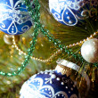Beautiful blue christmas decorations hanging on christmas tree with shiny glare - Stock Photo