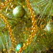 Beautiful green christmas decorations hanging on christmas tree with shiny glare — Zdjęcie stockowe