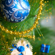 Beautiful painting christmas decorations hanging on christmas tree with shiny glare — Стоковая фотография