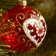 Beautiful red christmas decorations hanging on christmas tree with shiny glare — Stock Photo