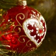 Beautiful red christmas decorations hanging on christmas tree with shiny glare - Stock Photo