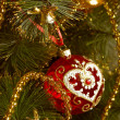 Beautiful red christmas decorations hanging on christmas tree with shiny glare — Lizenzfreies Foto