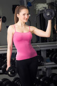 Smiling fitness woman with barbells — Stock Photo