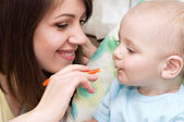 Young mother feeding baby boy — Stock Photo