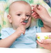 Mother's hand feeding baby boy — Stock Photo