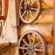 Village composition. Wooden wheels hanging on a wall of log house — Stock Photo #29271197