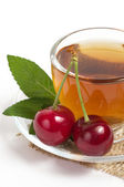 Fruit tea in cup with red cherry — Stock Photo