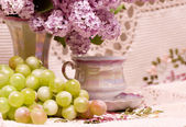 Vintage teacup with spring flowers and grape — Stockfoto