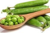Fresh green peas in spoon isolated on a white background — Stock Photo
