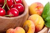 Schmackhafte aprikose und kirsche in holzschale — Stockfoto