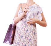 Beautiful pregnant woman with shopping a white background — Stock Photo