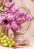 Vintage teacup with spring flowers and grape — Stock Photo