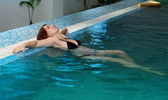 Pregnant woman sitting on the edge of the pool — Stock Photo