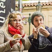 Young couple sitting eating pastry — Stock Photo