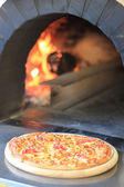 Pizza in a wooden oven — Stock Photo