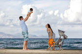 Happy family at the beach — Stok fotoğraf