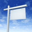 Blank White Real Estate Sign On a Blue Sky — Stock Photo #8861330
