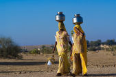 Women lugging water pot on head — Stock Photo