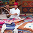 Постер, плакат: Craftsman uses handloom to produce rugs